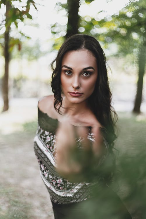 Confident young woman reaching hand towards camera in park