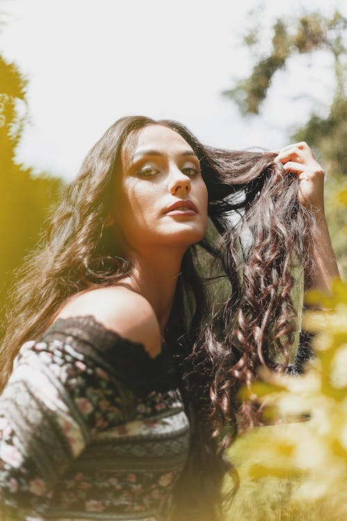 Side view of gorgeous young female in stylish dress touching long wavy hair and looking at camera while chilling in nature on sunny day