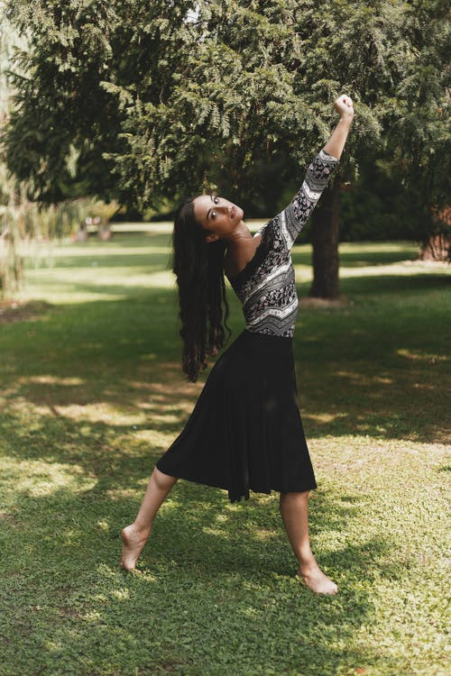 Full body side view of dreamy young woman with long dark wavy hair in shirt and skirt looking at camera while dancing in park with arms raised