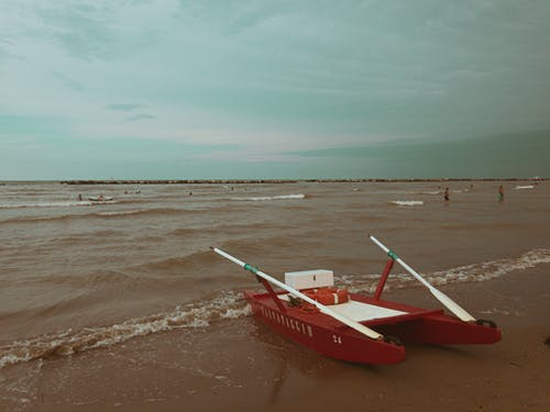 Rowing catamaran on wet sandy shore with tourists swimming in waving sea in cloudy weather