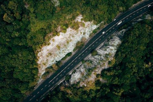 Asphalt road through green rocky valley