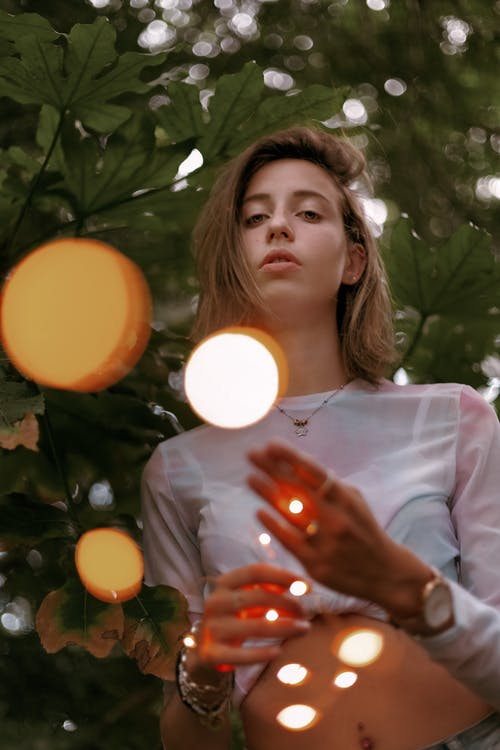 Low angle of content millennial female holding string of fairy lights in hands looking at camera in nature