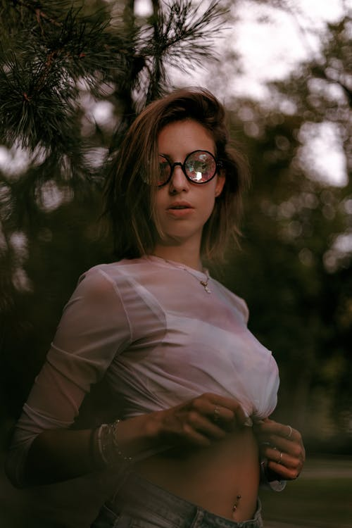 Woman in White Long Sleeve Shirt and Brown Pants Wearing Black Sunglasses