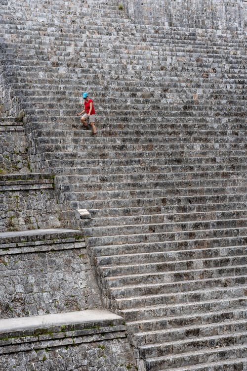 Woman in Red Shirt and Black Pants Walking on Stairs