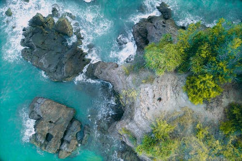 Drone view of foamy sea waves rolling near rocky cliff covered with green plants