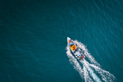 Top view of vessel sailing fast in deep waters of turquoise endless ocean