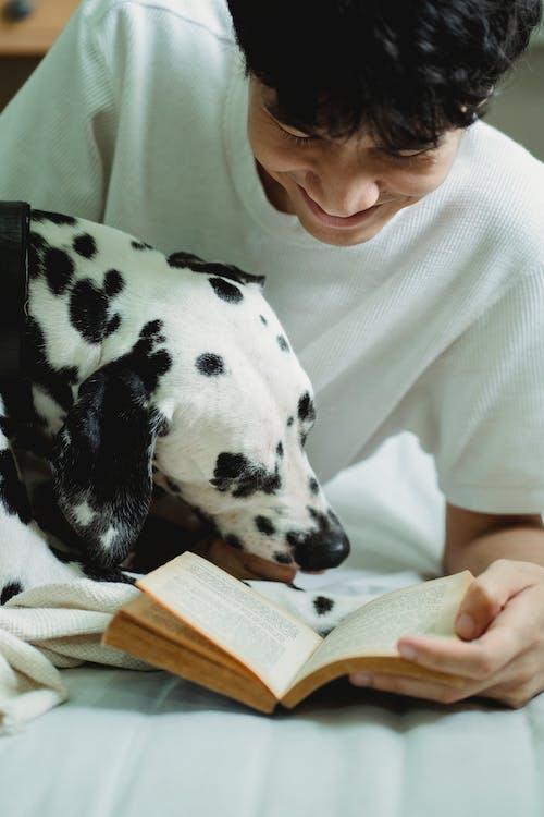 Woman in White Shirt Hugging Dalmatian Dog