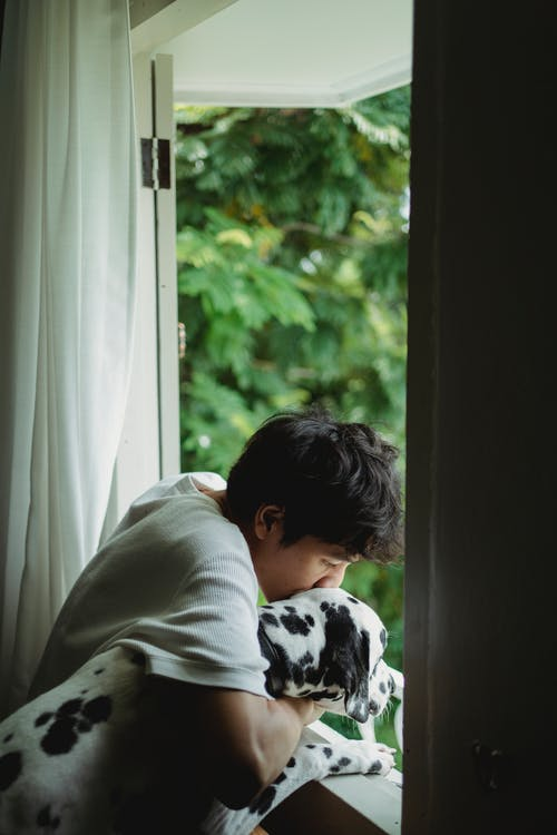 Woman in White and Black Floral Shirt Looking Out the Window