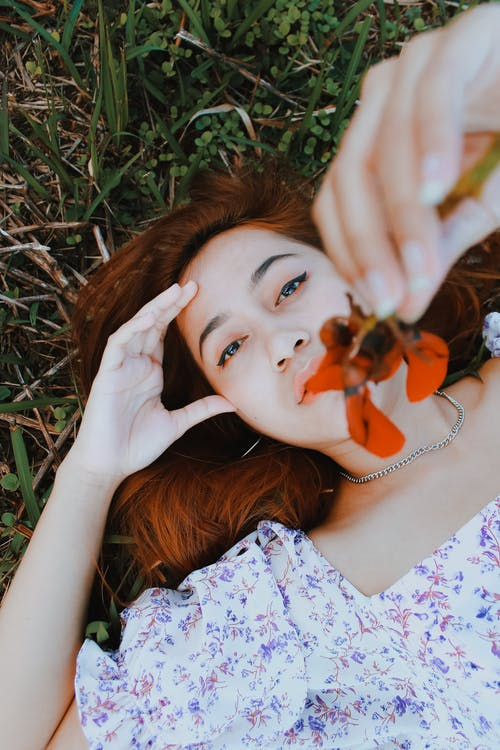 Stylish woman showing red flower on meadow