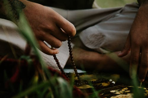 Faceless ethnic male with tattoo using dark brown prayer beads while praying on carpet on grass