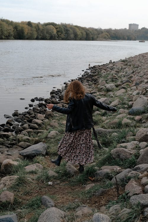 From above back view of anonymous trendy female strolling on rough stone coast near rippled river