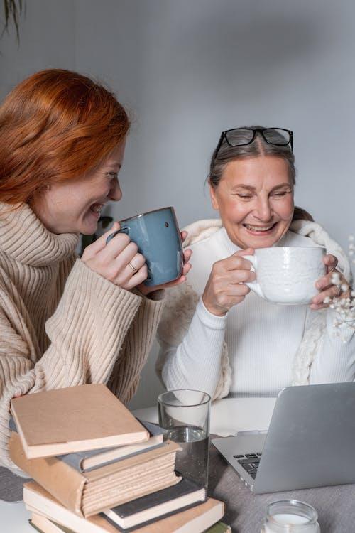 Woman in White Sweater Holding Blue Ceramic Mug
