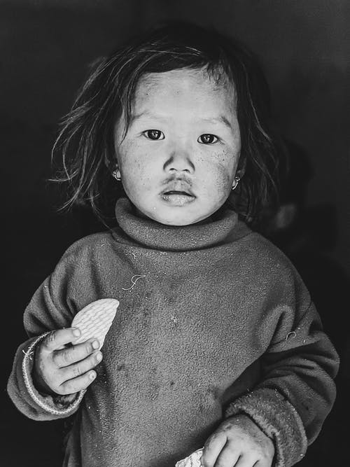 Grayscale Photo of Child in Sweater