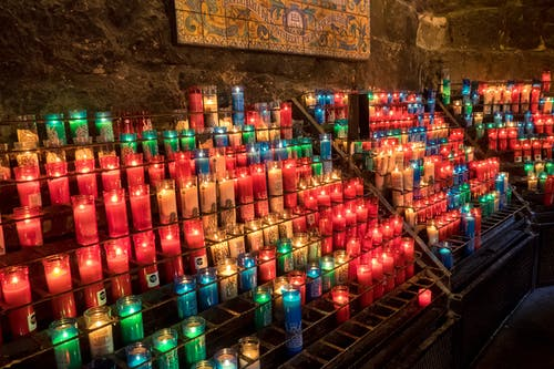 Colorful Lighted Candles Inside the Monastery