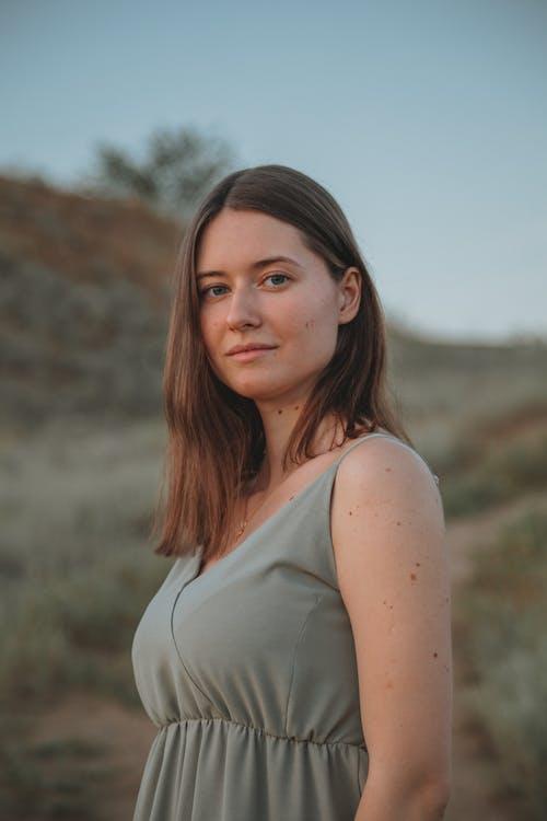 Calm woman in dress standing in field
