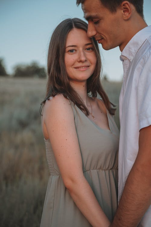 Side view of crop happy young man and woman in casual clothes holding hands while resting on meadow in countryside
