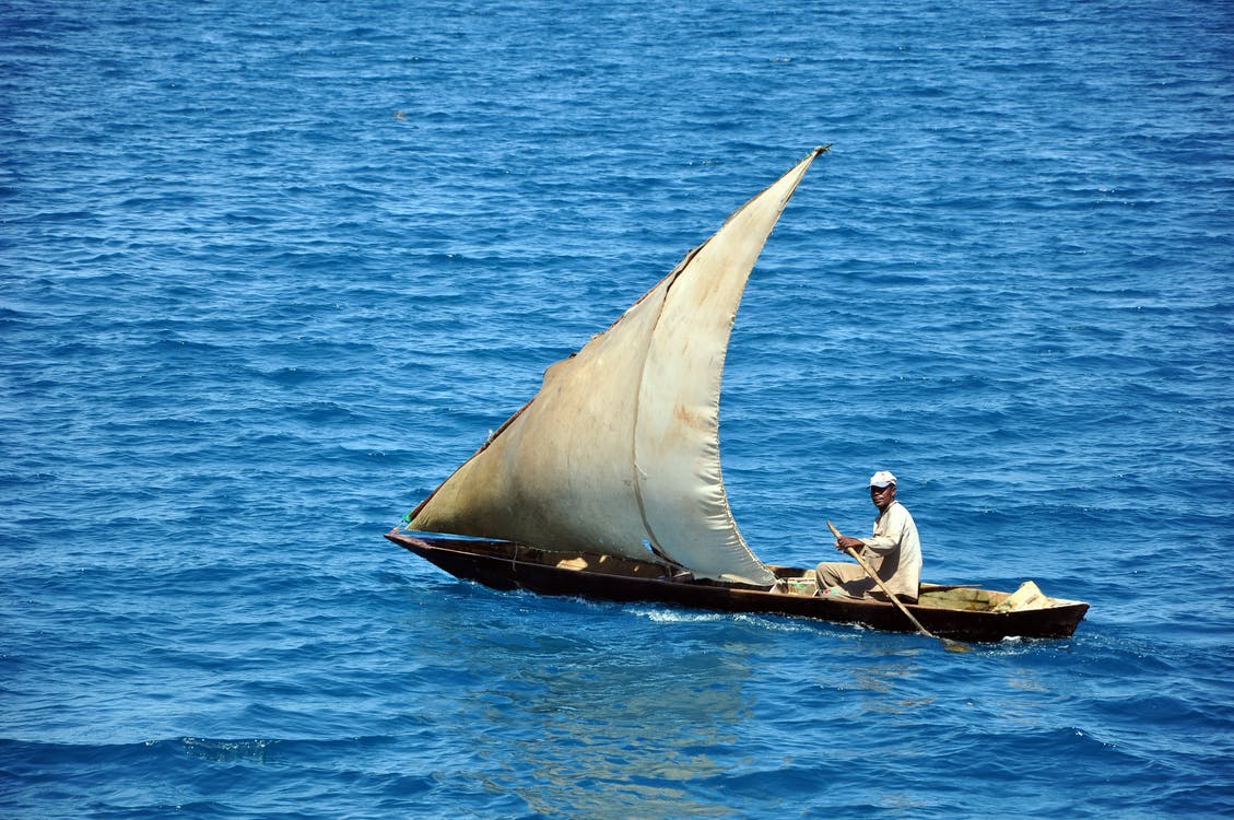 Man and Woman Sitting on Brown Boat on Blue Sea