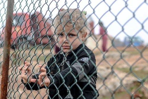 Little ethnic boy standing near net fence