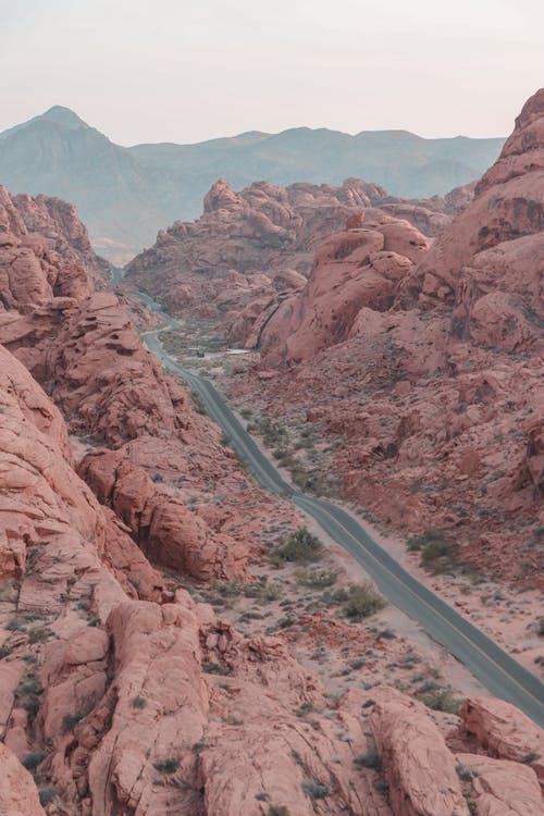 From above of narrow asphalt highway running between rocky formations in canyon in daylight in summer day in nature outside