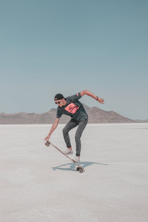 Man in Black T-shirt and Black Pants Riding on Black and Red Ski Blades