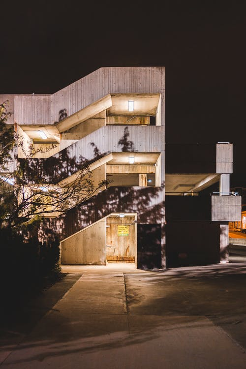 Contemporary house exterior with glowing lights and tree shadows on walls near walkway in evening