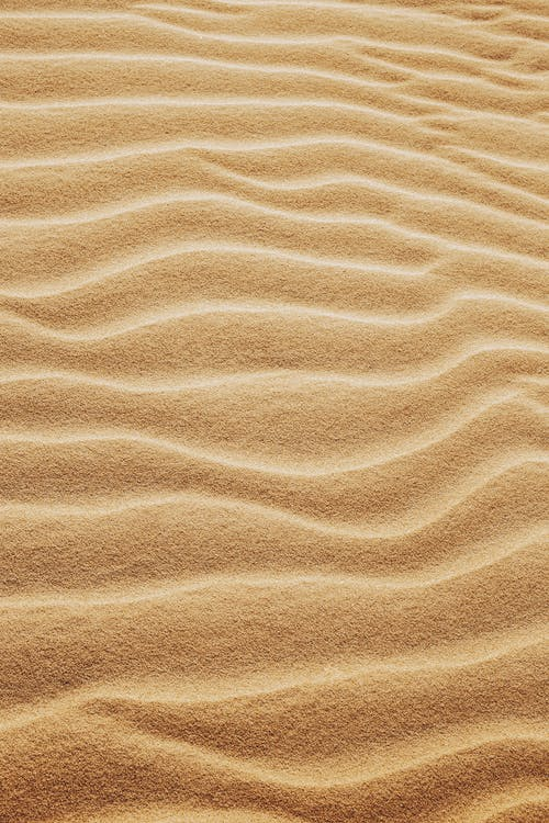 From above of fine wavy yellow sand spreading on smooth surface in hot sunny summer day