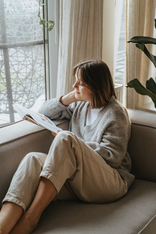 A Woman Reading a Book on a Couch