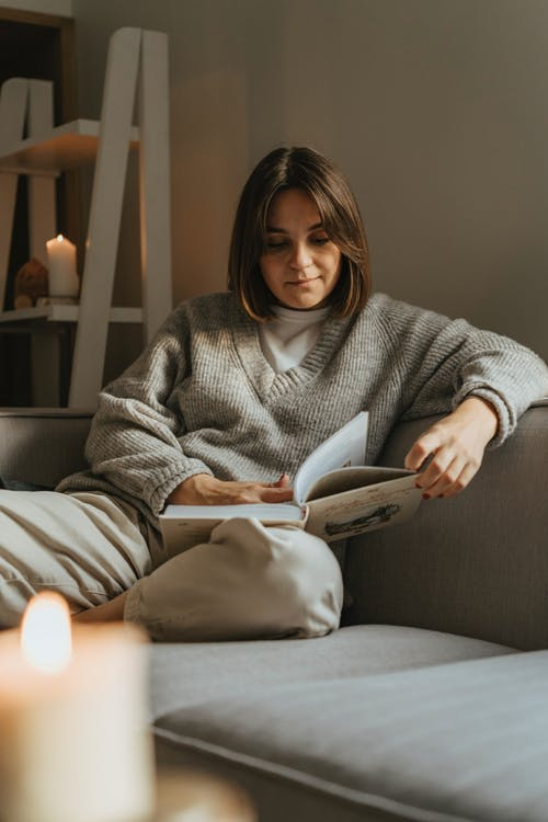 Woman in Gray Sweater Sitting on Gray Couch