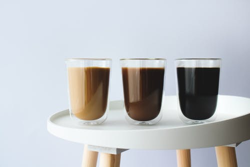 2 Brown and Black Drinking Glasses on White Wooden Table