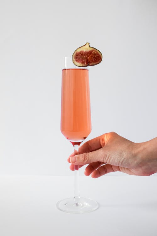 Person Holding Clear Drinking Glass With Orange Liquid