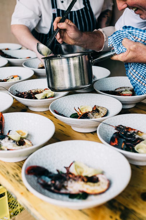 Unrecognizable coworkers with pot and ladder serving fresh seafood in various bowls while standing at table during work in restaurant