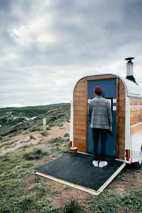 Unrecognizable person near trailer on hill