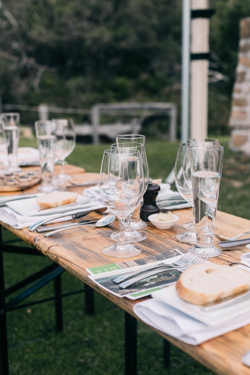 Banquet table with dishware in backyard