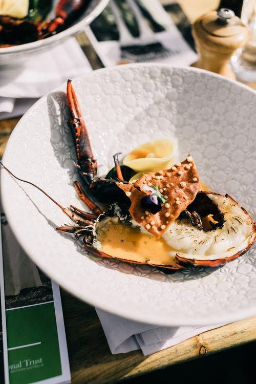 From above of appetizing fresh lobster served on white plate on table near seasoning n luxury restaurant with gourmet food