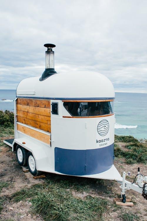 White trailer on grassy shore