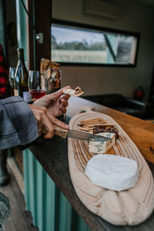 Anonymous person with knife cutting blue cheese on wooden board near camembert cheese while standing at counter of trailer with alcohol drinks on street