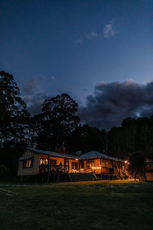 Illuminated house near trees at twilight time
