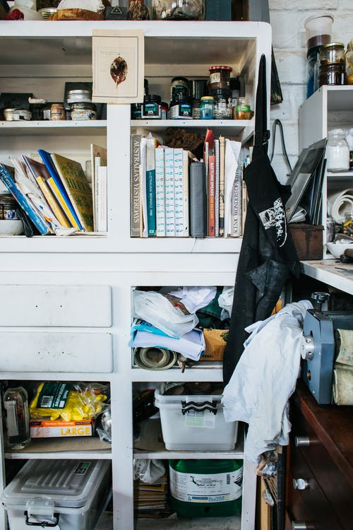 White cupboard with collection of books and abundance of assorted materials and supplies placed on shelves with containers in professional studio