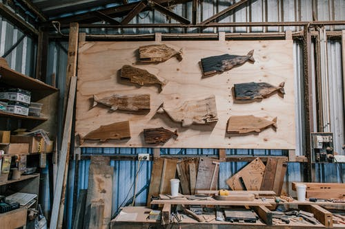 Whale shaped wooden blanks on board in professional carpentry studio with various special instruments and wooden planks near workbench with tools