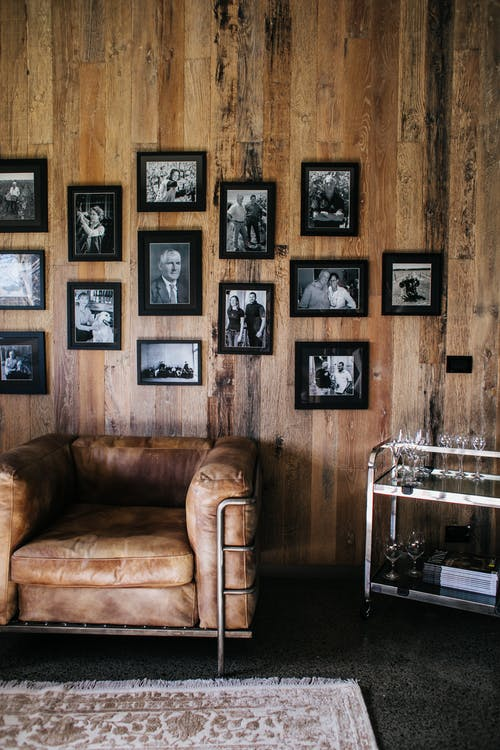 Various old framed photos hanging on wooden wall near comfortable armchair in vintage styled room with carpet an decorations