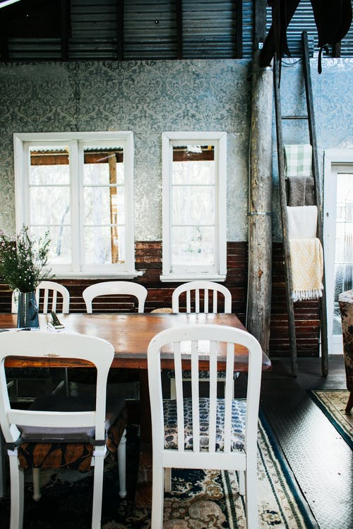 White chairs at wooden table with vase of fresh flowers placed in old fashioned cafeteria with rug against windows near doorway