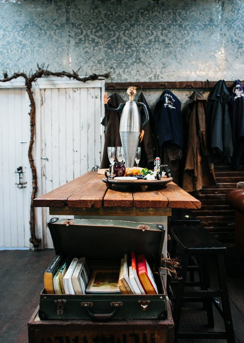 Vintage styled studio with table and aged suitcase with books