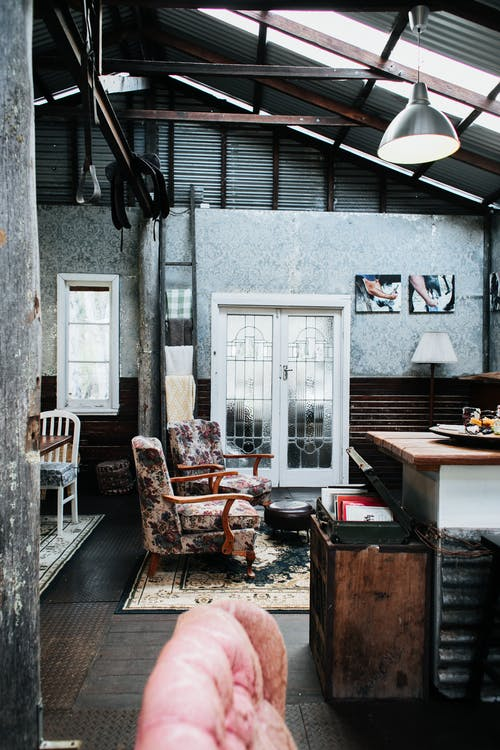 Interior of vintage studio with decorations on wallpaper and armchairs placed on rug in light room with old suitcase on wooden cupboard