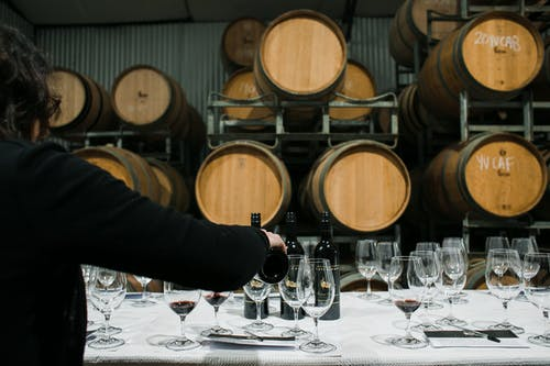 Back view of anonymous sommelier pouring wine from bottle into wineglass while standing at table with glassware in winery against barrels