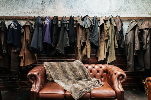 Various outerwear hanging on hooks at wall with wallpaper in light vintage studio with brown leather sofa with soft plaid