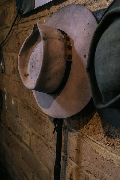 Vintage hats hanging on wall in rural house