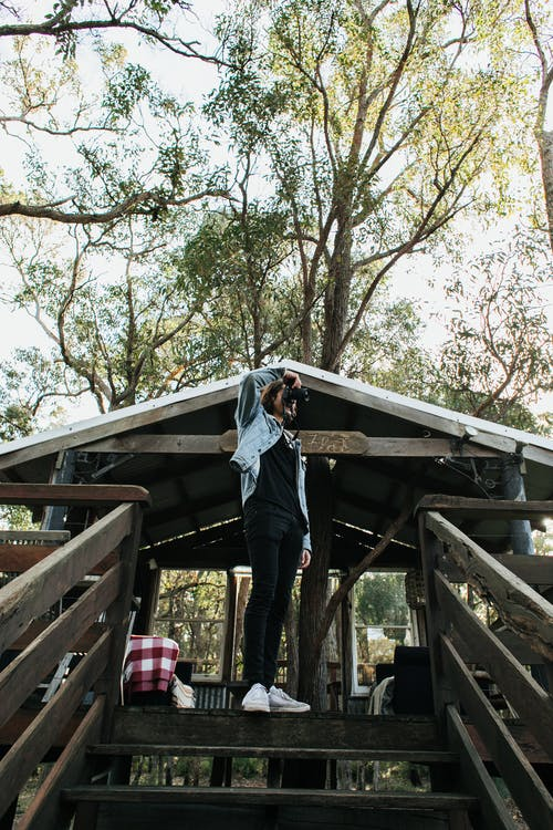 From below full body of anonymous female with taking picture on photo camera while standing on stairway of wooden gazebo