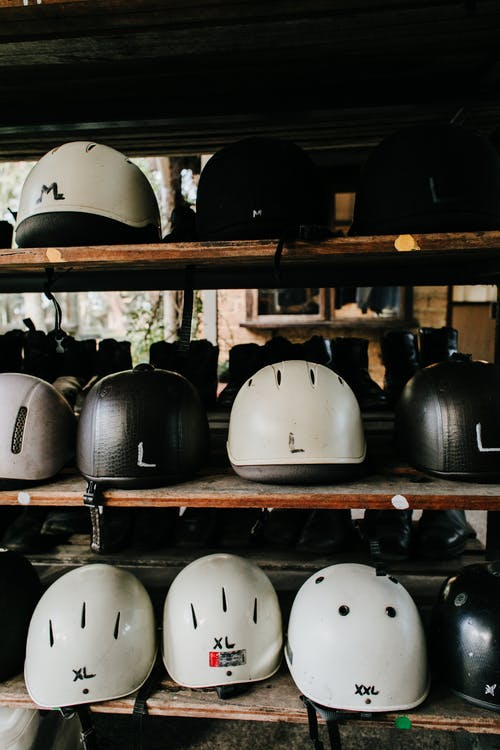 Abundance of white and black plastic helmets for safe riding placed on wooden shelves for rent on street in city