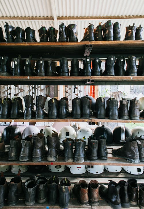 Abundance of leather old fashioned boots placed on wooden shelves near plastic protective helmets for rent on street in city