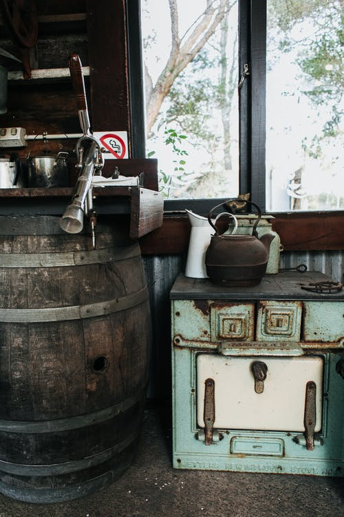 Aged kettle and dishes placed on old cooker near weathered barrel at window in vintage styled room in suburb area